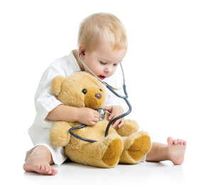 Toddler playing doctor with stuffed teddy bear.